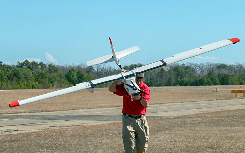 Jim Alexander from UMD's UAS Test Site carries a Talon 120 to the operation launch site.