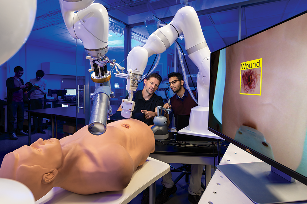 Assistant Professor Axel Krieger, at left, and master's student Anirudh Topiwala test a new robotic system for remote trauma assessment. Photo: John T. Consoli