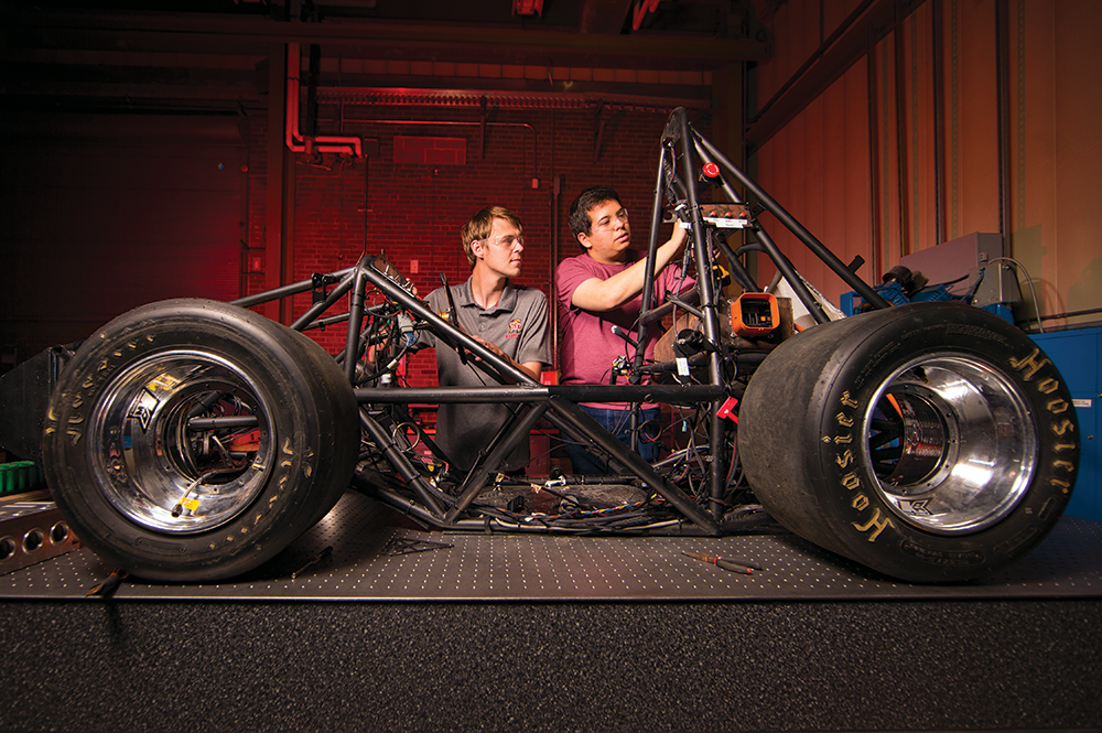 Terps Racing members Preston Der (left) and Garrison Case with the electric racecar. Photo: John T. Consoli
