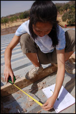 Civil engineering sophomore Kana Matsui measures dimensions for the installation of a solar panel array.  Photo by Elisabeth Smela.