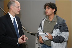 Ray O. Johnson speaks with a student after his talk. (Photo by Al Santos)