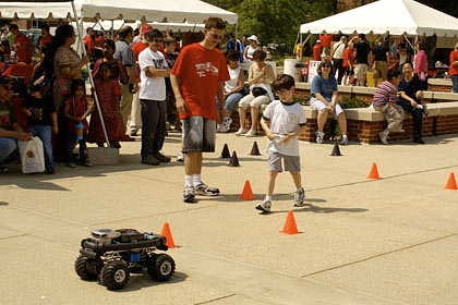 ECE student John Karvounis (center, red shirt) helps guide a Maryland Day visitor through the Maryland Cooperative Autonomous Vehicle System (MVACS) race track.