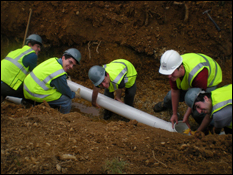 Students from the Anacostia Project team place the outflow pipe from the bioretention facility into the trench before it is filled back over with dirt. (Photo by Kristen Markham)
