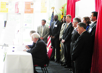 UM's Pres. Mote and Ray O. Johnson of Lockheed Martin sign the agreement as members of both organizations look on.