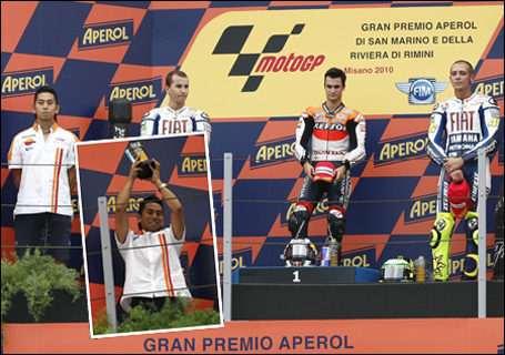 Main photo: Honda Racing won the 2010 MotoGP in the Italian Grand Prix. On the podium, the Honda racer is at center right, with the first-place trophy at his feet. Tax Yokoyama is at far left. Inset: Tax holds the trophy aloft.