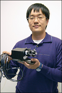 BioE graduate student Chia-Pin Liang holding the prototype Doppler Optical Coherence Tomography (DOCT) probe, which is designed to help surgeons navigate the brain and avoid damage to its blood vessels. Liang says that with further development, a handheld version could be created for other kinds of procedures in which doctors must guide tools deep into the body.