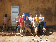 Most of the team with the clinic staff standing in front of the filter tanks.