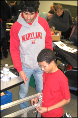 Vikas Bhatia, a junior in Chemical Engineering, helps a high school student at the FIRST build event on campus, Jan. 14, 2012.