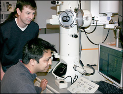 Associate Professor John Cumings (standing) and Khim Karki (seated) working with a transmission electron microscope.