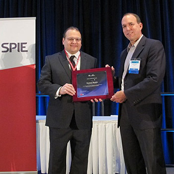 Prof. Christopher Lynch of UCLA (right) presents the  SPIE Smart Structures and Materials Lifetime Achievement Award to Prof. Norm Wereley (left) at the SPIE SS/NDE Symposium on March 12, 2013.