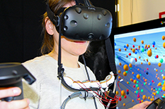 A prototype device attached to a virtual reality headset wafts scents toward the nose of Andrea Batch, a doctoral student in information studies developing technology to integrate smell into VR technology.(Photo courtesy of Andrea Batch and Biswaksen Patnaik)
