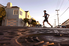 Runner and writer Rickey Gates pounds the pavement through San Francisco. High school buddy Michael Otte, below, assistant professor of aerospace engineering, used his research background to help seek efficient routes. Gates' completed run on every street in the city is traced in blue on a Strava heat map. (Running photo and map courtesy of Rickey Gates; Michael Otte photo courtesy of Clark School of Engineering)