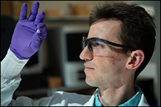 Rice University graduate student Sean Bittner holds a sample of a 3D-printed scaffold that may someday help heal osteochondral injuries of the kind often suffered by athletes. The material mimics the gradient structure of cartilage to bone found at the end of long bones. Photo by Jeff Fitlow