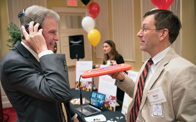 University of Maryland School of Dentistry Dean Mark Reynolds, DDS, PhD, MA, experiences what hearing sounds is like with a cochlear implant with Matt Goupell, PhD, associate professor in the Department of Hearing and Speech Sciences at College Park.