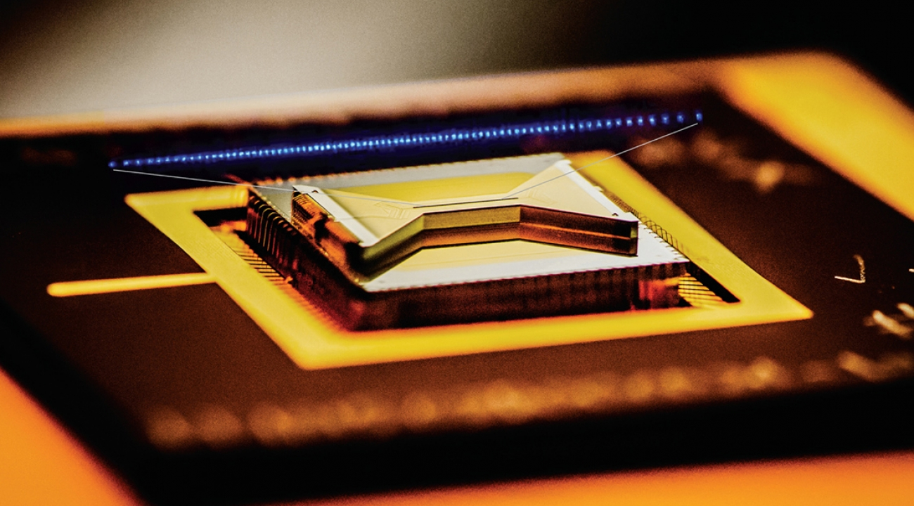 A semiconductor chip ion trap, fabricated by Sandia National Laboratories and used in research at the University of Maryland, composed of gold-plated electrodes that suspend individual atomic ion qubits above the surface of the bow-tie shaped chip. (Credit: Chris Monroe/JQI and Duke University)