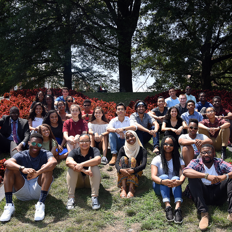 A group of diverse students poses seated on grass for a photo outside.