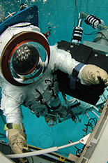 A diver works on a model of the Hubble Telescope, assisted by the Ranger robot.