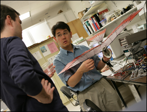 Dr. Horiuchi explains the workings of a micro-air vehicle to one of his students.