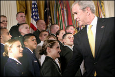 President George W. Bush congratulates newly commissioned member, Leslie Woll, undergraduate aerospace engineering student, of the Joint Reserve Officer Training Corps - White House photo by Eric Draper