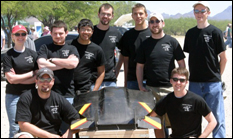 "2006-2007 UMD DBF Team.  Back row:  Leslie Woll, Lucas Parker, Chris Cheok, Robbie Vocke, Tim Spiridonov, Brian Donnelly, Chris Plumley.  Front Row:  Mentor and pilot Evandro Valente, the UMD ""Flying Flapjack,"" and Steve Myers."