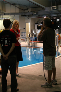 Fox 5 reporter Holly Morris interviews the Robotics@Maryland team inside the Neutral Buoyancy Research Facility.
