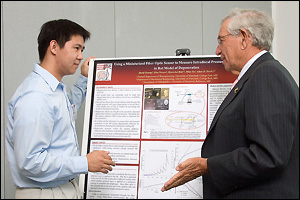 Dr. Robert E. Fischell (right) talks to graduate student David Hwang about his research.