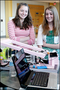 Team Daedalus Project members Yelena Leznik (left, chemical and biomolecular engineering) and Michelle Stanton (mechanical engineering) with their hovercraft. It must follow a line, activate and pass through a gate, and navigate around several turns in a specially-designed course. The craft is not remote controlled but autonomous—it must accomplish these tasks using only the sensors, computer and equipment the students designed for it.