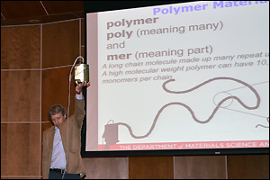 Professor Robert M. Briber demonstrating the molecular structure and relative size of a polymer molecule using his