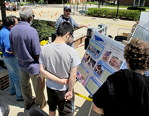 Visitors speak with Director of Technical Operations Bryan Quinn about the solar array that powered exhibits and demonstrations on the Kim Plaza during Maryland Day.