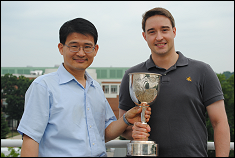 Dr. Yunho Hwang, CEEE Associate Director and Magnus Eisele, ME Ph.D. Candidate with the SAE/IMechE Best Technical Paper Award Trophy.  Photograph by Elizabeth Baugher