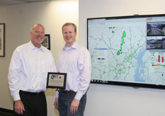 Pictured is President & CEO of ITS America, Scott Belcher (on left) and Michael L. Pack (on right), CATT Lab Director at the ribbon cutting of their interactive display in the ITS America offices in Washington, D.C.