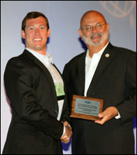 Matt Mosteller receives the award from INCOSE President John Thomas.