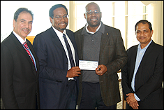 Alumnus Dunstan Macauley '02, (second from the right), presents the check in support of the ASHRAE Scholarship Fund to Dean Darryll Pines, Farvardin Professor & Dean (second from the left), with Professors Michael Ohadi (left), and B. Balachandran, Minta Martin Professor & Chair of Mechanical Engineering (right).