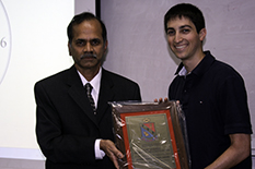 Eta Kappa Nu President Daniel Silversmith accepts the award from Department Chair Rama Chellappa.