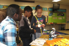 Malick Diarra works with students at Greenbelt Elementary School on building robots.