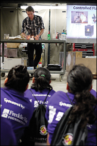 Ph.D. candidate Isaac Leventon explaining basic fire science to elementary school students from the America Reads*America Counts program.